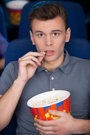 What a great movie! Excited young man eating popcorn and watching movie while sitting at the cinema  photo