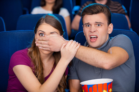 Scary moment. Shocked young couple watching a scary movie together while sitting at the cinema  photo