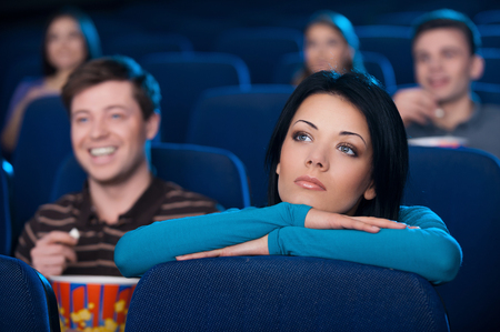 spectator: Feeling lonely at the cinema. Bored young woman watching movie at the cinema
