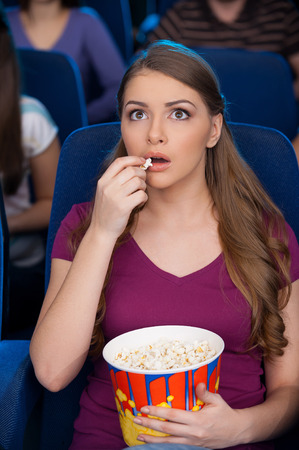 eating popcorn: It is my favorite moment. Beautiful young woman eating popcorn and watching movie while sitting at the cinema  Stock Photo
