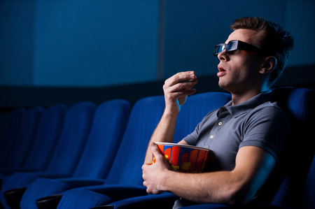 Watching three-dimensional movie. Excited young man in three-dimensional glasses eating popcorn and watching movie while sitting at the cinema