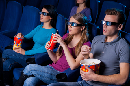 Enjoying three-dimensional movie. Top view of people in three-dimensional glasses watching movie while sitting at the cinema  photo