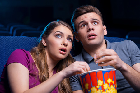 horror movie: This movie is so scary! Shocked young couple eating popcorn and watching movie together while sitting at the cinema  Stock Photo