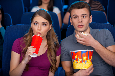 What an exciting movie! Excited young couple eating popcorn and drinking soda while watching movie at the cinema  photo