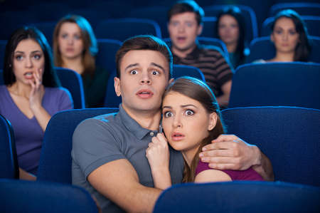 fear woman: Watching horror movie. Shocked young couple bonding to each other while watching movie at the cinema