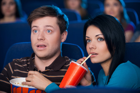 eating popcorn: This movie is so exciting! Excited young couple eating popcorn and drinking soda while watching movie at the cinema  Stock Photo