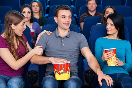personas discutiendo: Ligue en el cine. Hombre joven que se sienta junto con su novia y la celebración de la mano en la rodilla a otra mujer mientras ve la película en el cine