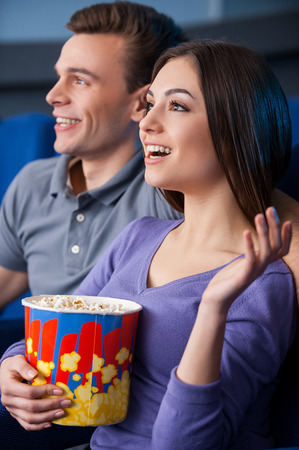 What an exciting movie! Side view of happy young couple eating popcorn while watching movie at the cinema  photo