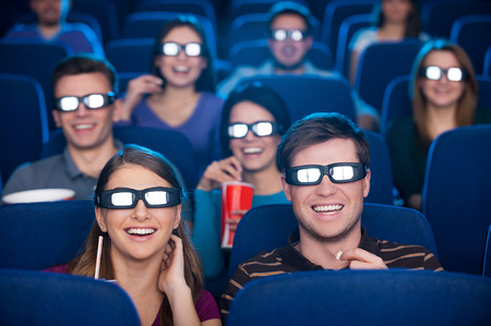 theater audience: Watching three-dimensional movie. Happy young people in three-dimensional glasses watching movie at the cinema together Stock Photo