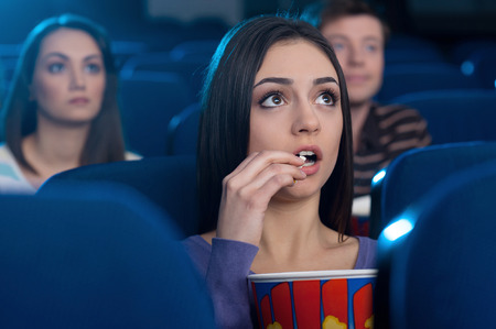 theater popcorn: Woman at the cinema. Attractive young woman eating popcorn and watching movie while sitting at the cinema
