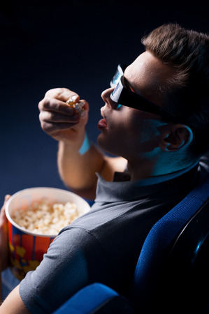 It is so realistic movie! Top view of excited young man in three-dimensional glasses eating popcorn and watching movie while sitting at the cinema  photo