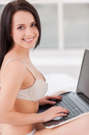 Surfing web in bed. Side view of beautiful young woman in lingerie sitting on bed with laptop and looking over shoulder  photo