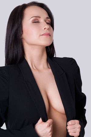 Woman with beautiful cleavage. Attractive young woman with beautiful cleavage standing against grey background and adjusting her suit photo