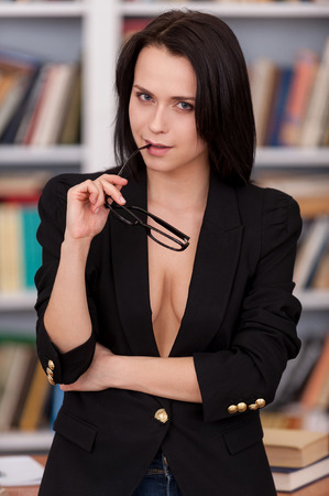 Confident and teacher. Beautiful young woman in suit over the body holding glasses and looking at camera while standing against book shelf