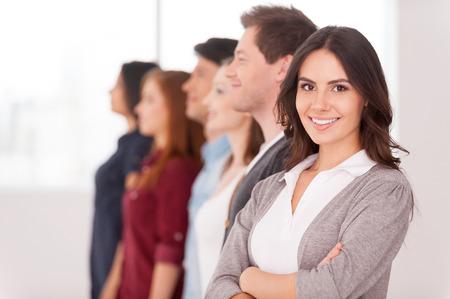 mani incrociate: Leader sicuro di sé. Attraente giovane donna con le braccia incrociate e sorridente, mentre un gruppo di persone in piedi dietro di lei in una riga