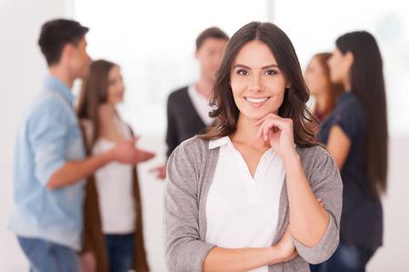 gente comunicandose: Mujer joven confidente que sostiene la mano en la barbilla y sonriente mientras que el grupo de personas que se comunican en el fondo