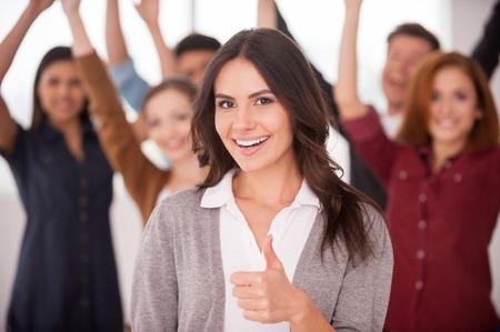 Bella giovane donna che mostra il pollice in alto e sorridente, mentre un gruppo di giovani felici in piedi sul fondo e mantenere le braccia Archivio Fotografico - 26712698
