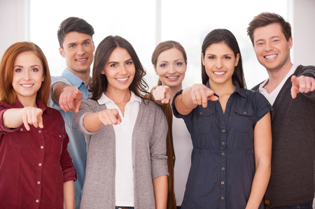 people  camera: Will you join our team? Group of cheerful young people standing close to each other and pointing you Stock Photo