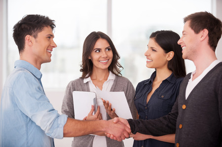 Welcome on board! Two cheerful young men handshaking while two women looking at them and smiling Stock Photo