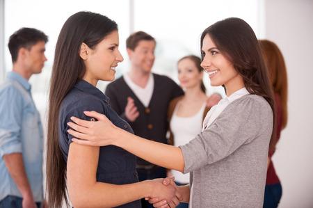 people communicating: Women handshaking. Two cheerful young women handshaking while group of people communicating on background Stock Photo