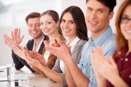 aplaudiendo: Aplaudiendo a usted. Grupo de jóvenes sentados juntos en la mesa y aplaudiendo a usted