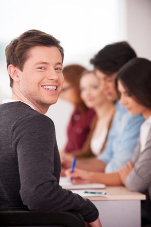 Confident in his team. Rear view of handsome young man looking over shoulder and smiling while sitting together at the table with another people  photo