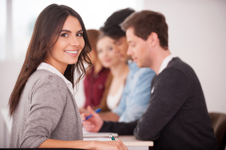 looking over shoulder: Confident in her team. Rear view of beautiful young woman looking over shoulder and smiling while sitting together at the table with another people