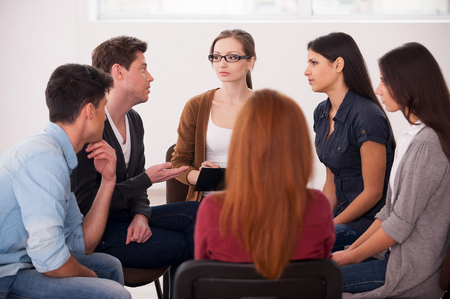 terapia grupal: La terapia de grupo. Grupo de personas que se sientan cerca unos de otros y se comunican