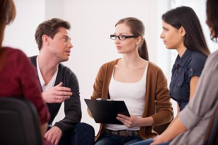 terapia grupal: Tengo un problema. Grupo de personas que se sientan cerca unos de otros, mientras que el hombre está diciendo algo y gesticulando
