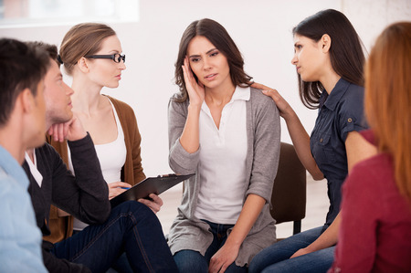 Tell us about your problem! Depressed young woman sitting close to other people and holding head in hand photo