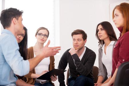 terapia grupal: Quiero compartir mi problema. Grupo de personas que se sientan cerca unos de otros, mientras que el hombre está diciendo algo y gesticulando Foto de archivo