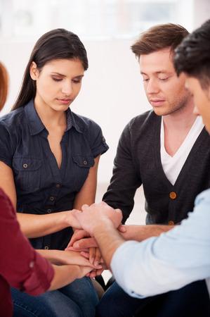 terapia grupal: La terapia de grupo. Grupo de personas que se sientan cerca unos de otros y de la mano juntos