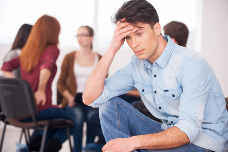 support group: Feeling pain and depression. Depressed young man sitting at the chair and holding head in hand while other people communicating on background
