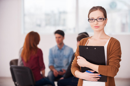 I will help you to solve your problems. Confident woman in glasses holding clipboard and looking at camera while group of people sitting on background photo