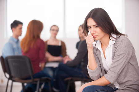 Feeling lonely and depressed. Depressed young woman sitting at the chair and crying while other people communicating on background  photo