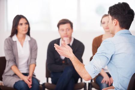 Het delen van zijn problemen met mensen. mensbeeld dat iets vertelt en gebaren terwijl groep mensen zitten voor hem en luisteren
