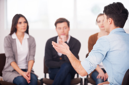 Sharing his problems with people. view of man telling something and gesturing while group of people sitting in front of him and listening photo