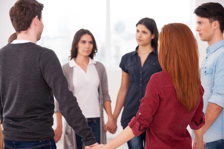 terapia de grupo: Confía en círculo. Grupo de personas de pie en círculo y tomados de la mano
