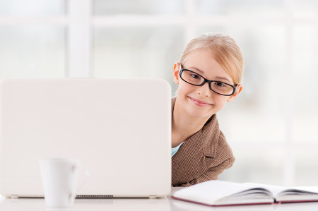 Small business. Cute little girl in glasses and formalwear looking out of the laptop and smiling while sitting at the table  photo