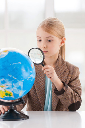 Examining globe. Concentrated little girl in formalwear examining globe with a loupe while sitting at the table photo
