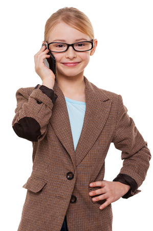 Talking about business. Cheerful little girl in formalwear talking on the mobile phone and holding hand on hip while standing isolated on white photo