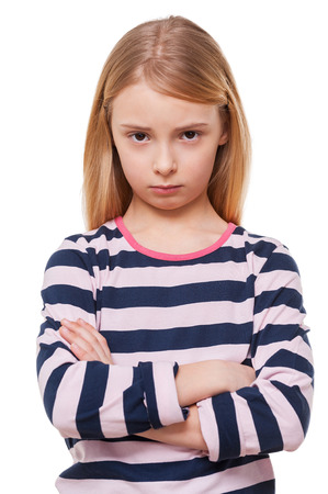 Sad little girl. Sad little girl keeping arms crossed while standing isolated on white photo