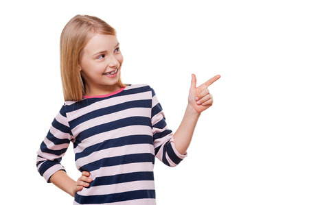 Showing the right direction. Cheerful little girl pointing away and holding hand on hip while standing isolated on white Stock Photo