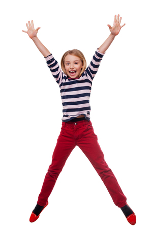 arms raised: Carefree child. Full length of happy little girl jumping while standing isolated on white