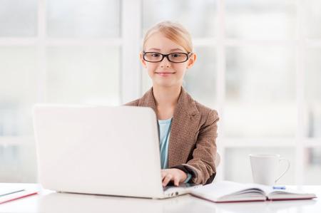 ni�as peque�as: Se�ora del negocio Little. Ni�a linda en gafas y ropa formal sentado en la mesa y utilizando equipo port�til Foto de archivo