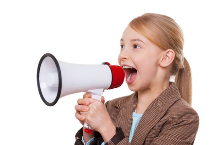 Announcing good news. Cheerful little girl in formalwear shouting at megaphone while standing isolated on white photo