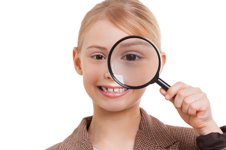 Examining you. Cheerful little girl in formalwear examining you with magnifying glass while standing isolated on white photo