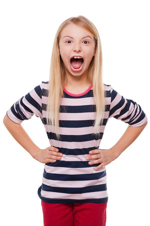 using voice: Furious little girl. Angry little girl shouting and holding hands on hip while standing isolated on white Stock Photo