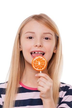 Girl with lollipop. Cheerful little girl licking lollipops and looking at camera while standing isolated on white Stok Fotoğraf