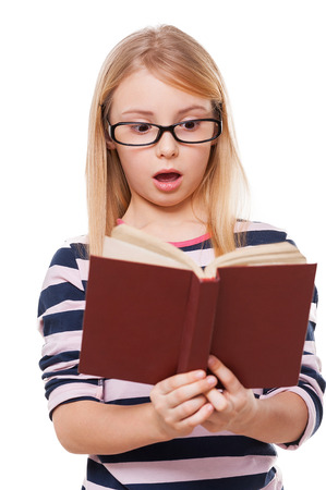 No way! Surprised little girl reading book and keeping mouth open while standing isolated on white photo